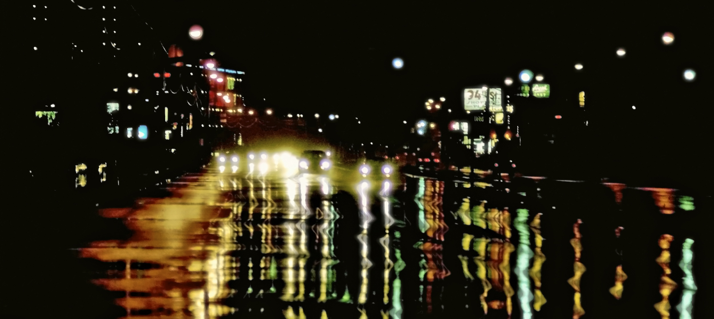photo of cars on wet road at nighttime
